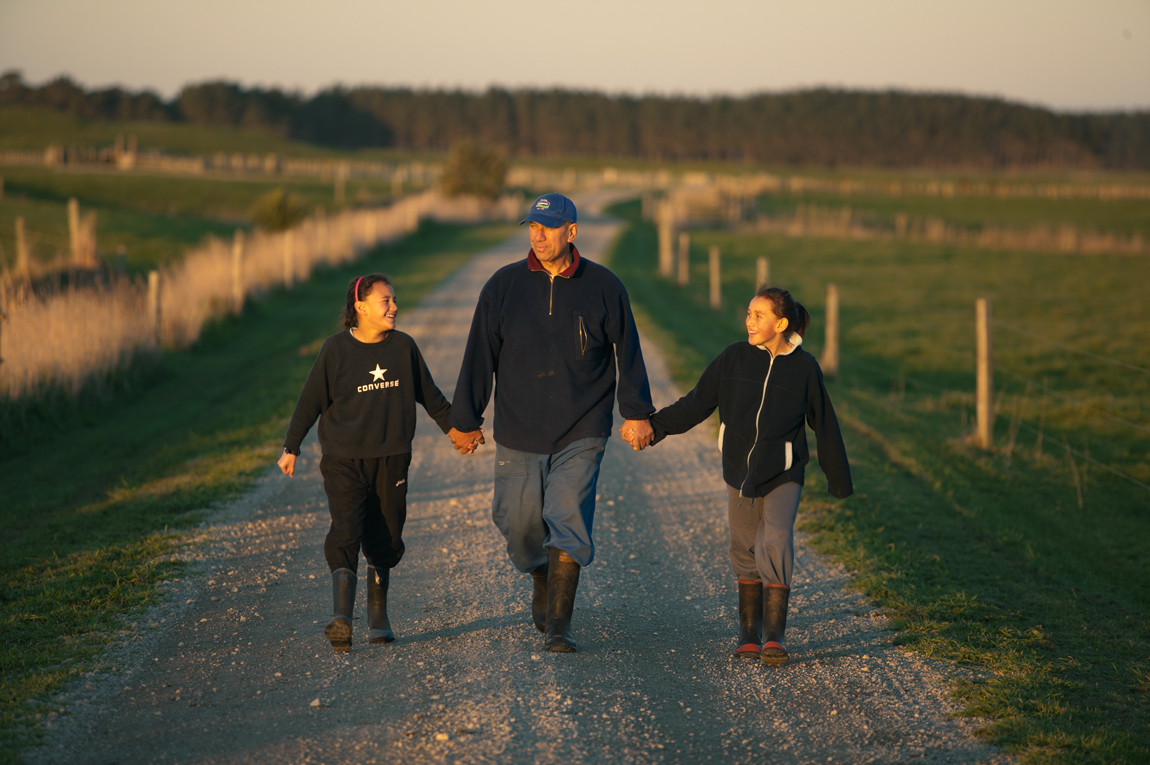 Guy_Robinson_people_photographer_auckland_father_farmer_holds_daughters_hands_walking